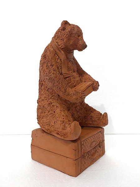 orso in terracotta seduto su una valigia